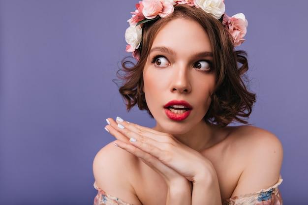 Portrait de gros plan de belle femme rêveuse avec des roses dans les cheveux. photo intérieure d'une fille merveilleuse en couronne debout.