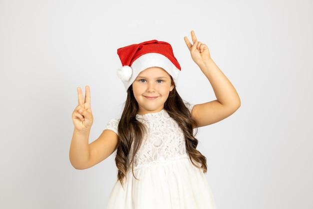 Portrait en gros plan d'une belle fille aux cheveux longs en robe blanche et chapeau de père noël rouge dansant et sho...