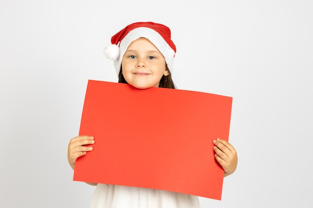 Portrait en gros plan d'une belle fille de six ans en chapeau de père noël tenant une affiche vide rouge isolée o...