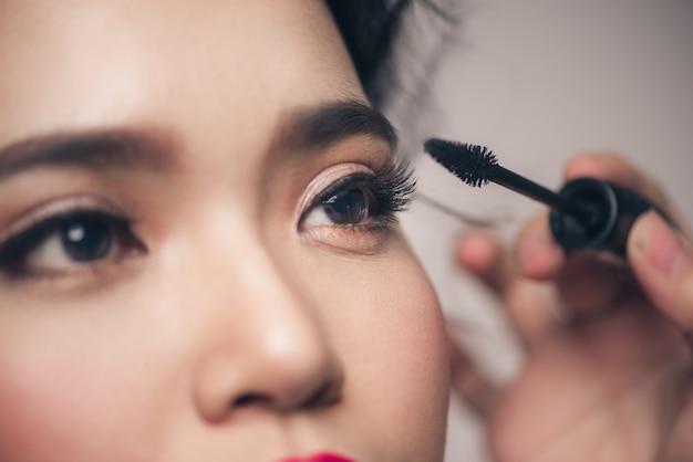 Portrait en gros plan de la belle fille touchant le mascara noir à ses cils