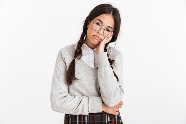 Portrait en gros plan d'une belle fille triste portant des lunettes en fronçant les sourcils et en soutenant sa tête isolée sur un mur blanc
