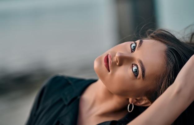 Portrait en gros plan d'une belle jeune brune aux cheveux longs marchant sur la plage au coucher du soleil. plaisir de la nature.