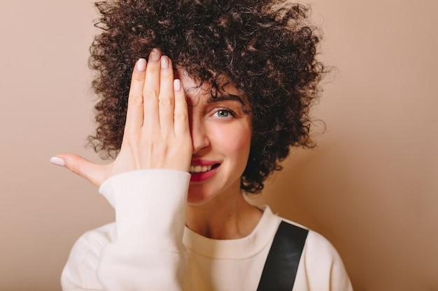 Portrait en gros plan de la belle jeune femme avec une coiffure courte et de grands yeux bleus fermés un côté face à la main sur beige