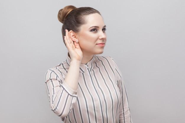 Portrait en gros plan d'une belle jeune femme drôle en chemise rayée et coiffure d'interdiction de collection brune, debout avec la main près de l'oreille et essayant d'écouter. tourné en studio intérieur, isolé sur fond gris.