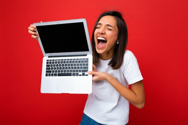 Portrait en gros plan de la belle jeune femme ravie et heureuse avec une courte coupe de cheveux brunet foncé tenant un ordinateur portable avec des yeux fermés portant un t-shirt blanc et un jean isolé sur fond de mur rouge. flic