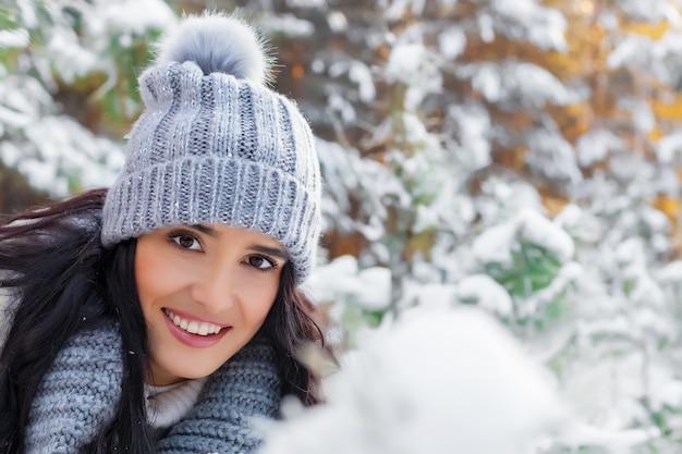 Portrait en gros plan d'une belle jeune femme souriante dans la forêt en hiver