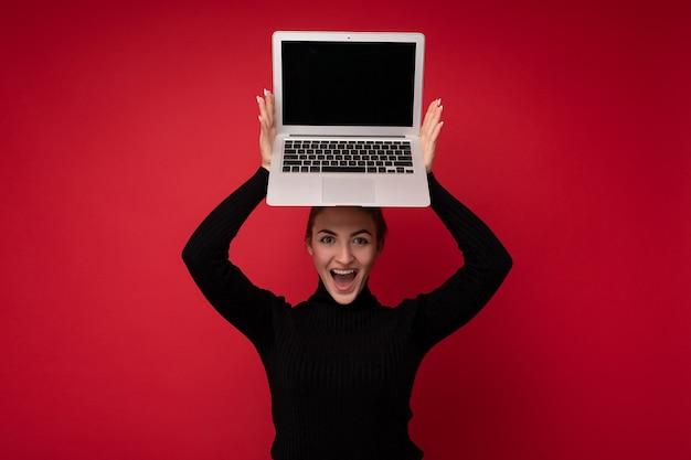 Portrait en gros plan d'une belle jeune femme souriante et heureuse avec des cheveux bruns réunis tenant un ordinateur