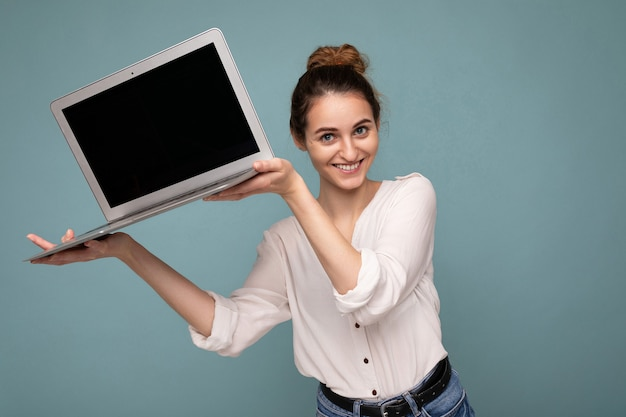Portrait en gros plan d'une belle jeune femme souriante et heureuse tenant un ordinateur portable en regardant la caméra