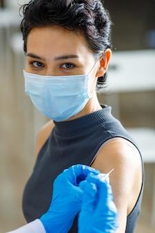 Portrait en gros plan d'une belle patiente aux cheveux noirs courts porte un masque facial assis regarde la caméra tout en recevant une injection de vaccin d'un médecin en blouse blanche et des gants en caoutchouc bleu.