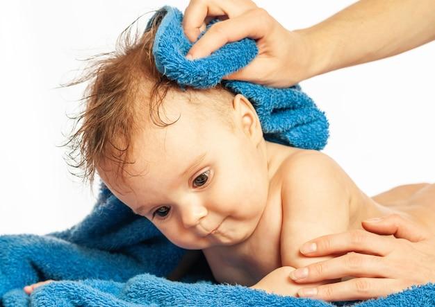 Portrait en gros plan d'une belle petite fille allongée sur une serviette après le bain sur fond blanc