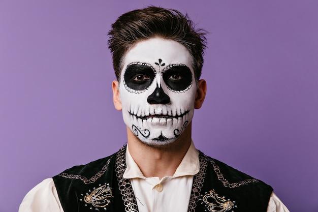 Portrait en gros plan de brunet avec visage peint pour halloween. mec aux yeux bruns en chemise blanche