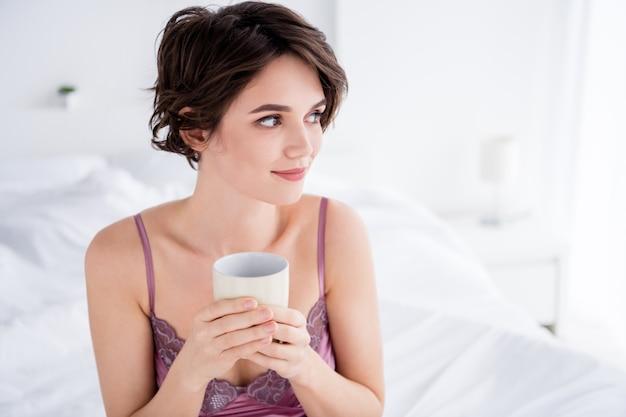 Portrait en gros plan d'une charmante charmante fille rêveuse buvant du café au lait