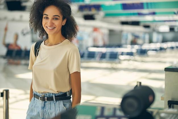 Portrait en gros plan d'une charmante femme en vêtements décontractés regardant et posant devant l'appareil photo à l'intérieur