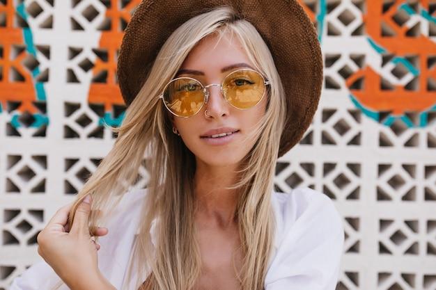 Portrait de gros plan de charmante fille européenne posant au resort avec un sourire doux. incroyable femme blonde jouant avec ses cheveux pendant une séance photo en extérieur.