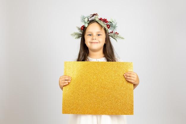 Portrait en gros plan d'une charmante fille souriante dans une guirlande de noël tenant une bannière vierge brillante dorée...