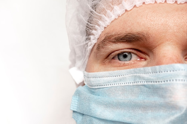 Portrait en gros plan d'un chirurgien expérimenté, médecin avec masque, prêt à travailler à l'hôpital. les yeux du docteur. covid-19 [feminine. pandémie. l'homme est en sécurité et fier de lui. concept de médecine, d'hôpital et de médecins