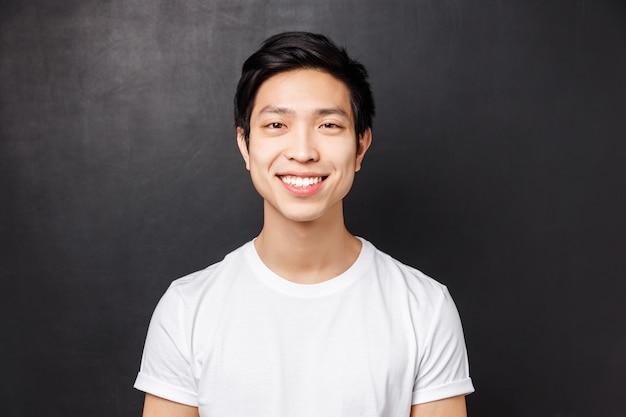 Portrait en gros plan d'un client asiatique satisfait souriant heureux, regardant la caméra, debout avec une attitude positive heureuse, concept d'émotions et de visages de personnes