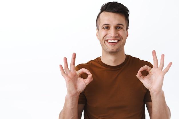 Portrait en gros plan d'un client masculin satisfait, heureux et souriant, d'un homme montrant des signes d'approbation, d'accord ou comme un service de bonne qualité fourni par l'entreprise, recommande le produit, mur blanc