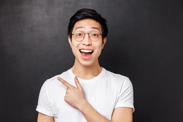 Portrait en gros plan d'un collègue asiatique enthousiaste ayant une conversation animée, discuter d'un événement ou d'un nouveau produit en stock, pointant le doigt dans le coin supérieur gauche ou derrière,