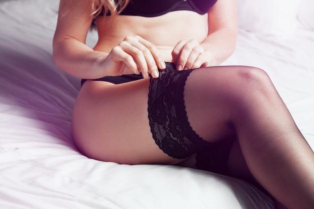 Portrait de gros plan d'un corps de femme sexy en lingerie noire et bas au lit