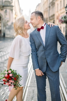 Portrait en gros plan d'un couple d'amoureux, bel homme de 50 ans en costume et nœud papillon, debout avec sa jolie femme en robe blanche avec bouquet de fleurs, sur fond de vieille ville