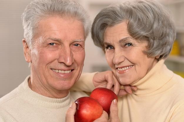 Portrait en gros plan d'un couple de personnes âgées heureux mangeant des pommes à la maison