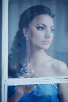 Portrait gros plan créatif d'une femme de la mode dans une magnifique robe romantique bleue