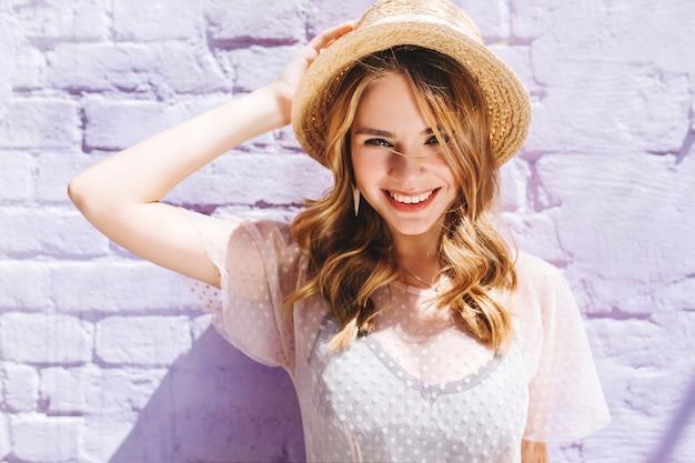 Portrait de gros plan de dame blonde heureuse avec un large sourire posant en journée ensoleillée près du vieux mur
