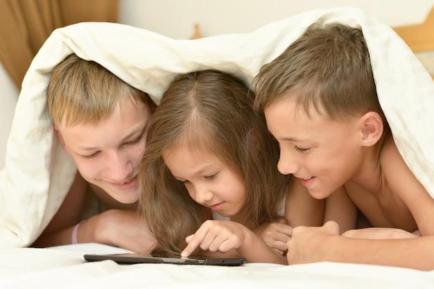 Portrait en gros plan de deux frères et d'une petite soeur avec tablet pc