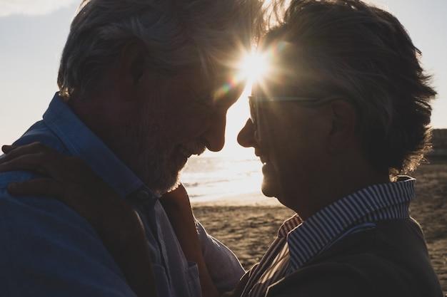 Portrait et gros plan de deux personnes âgées heureuses et amoureuses dansant en souriant avec le soleil du coucher de soleil entre leurs têtes
