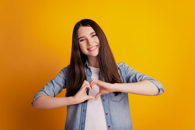 Portrait en gros plan de doigts de femme montrent le symbole du coeur humeur romantique isolé fond de mur jaune