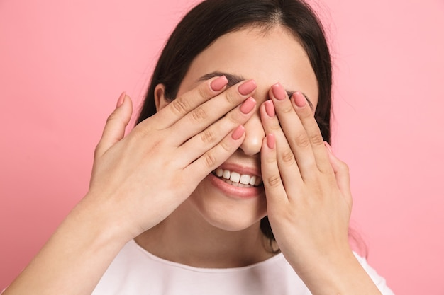 Portrait en gros plan d'une douce fille joyeuse avec de longs cheveux noirs couvrant ses yeux et jetant un coup d'œil si les mains isolées sur le mur rose