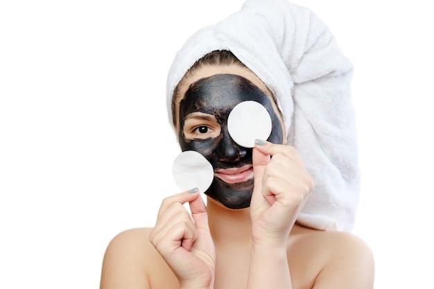 Portrait en gros plan drôle belle femme avec masque facial noir sur fond blanc, fille avec une serviette blanche sur la tête, sourire satisfait et heureux, a couvert ses yeux de boules de coton
