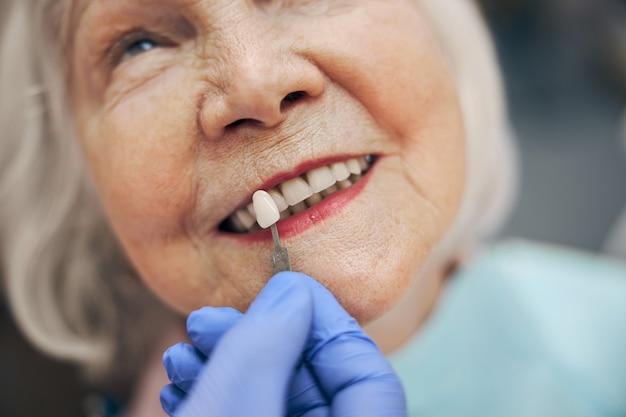 Portrait en gros plan du dentiste vérifiant et sélectionnant la couleur des dents tout en effectuant le processus de traitement dans la clinique professionnelle