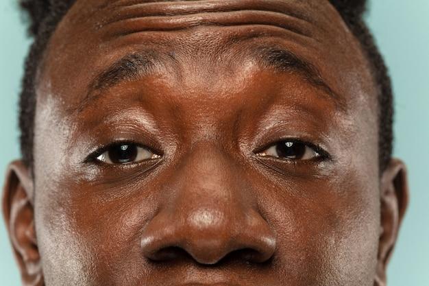Portrait en gros plan du jeune homme afro-américain sur fond bleu studio. beau modèle masculin avec une peau bien entretenue. concept d'émotions humaines, expression faciale, ventes, publicité. yeux et joues.