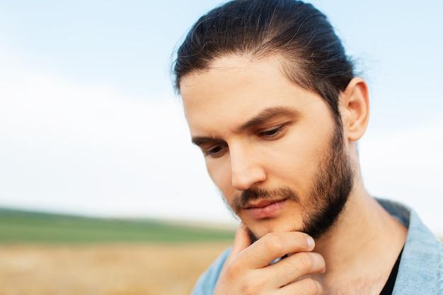 Portrait de gros plan du jeune homme regardant vers le bas, touchant le menton avec la main.