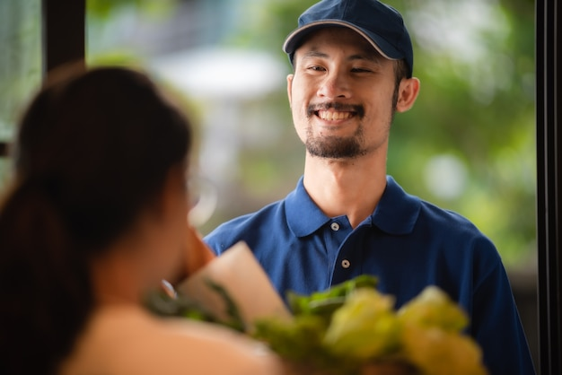 Portrait en gros plan du livreur, gars souriant en uniforme de t-shirt bleu, produits d'épicerie en ligne, nouveau concept de mode de vie normal, commerce électronique de magasin de détail, vie urbaine, transport de livraison.