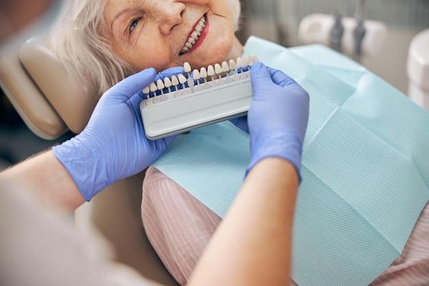 Portrait en gros plan du médecin choisissant la couleur d'un membre artificiel dentaire avec une patiente à la clinique dentaire