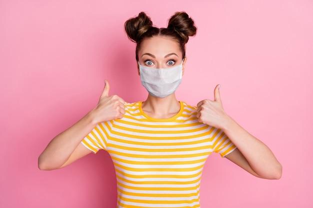 Portrait en gros plan d'elle elle belle jolie fille en bonne santé portant un masque de sécurité montrant la médecine à double pouce aide aide mers solution de thérapie cov soins de santé isolé fond de couleur rose pastel