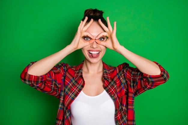 Portrait en gros plan d'elle elle belle jolie fille joyeuse et gaie en chemise à carreaux montrant un signe ok comme des lunettes taquinant la langue trompant isolé sur fond de couleur vert vif brillant éclatant