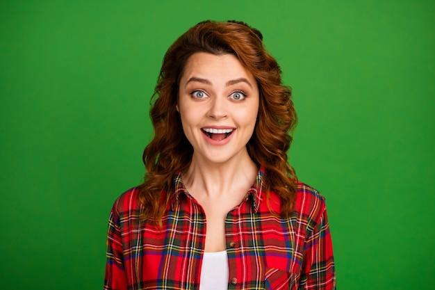 Portrait en gros plan d'elle, elle belle jolie jolie fille aux cheveux ondulés joyeuse et émerveillée, vêtue d'une chemise à carreaux, une excellente nouvelle isolée sur un fond de couleur vert vif et brillant
