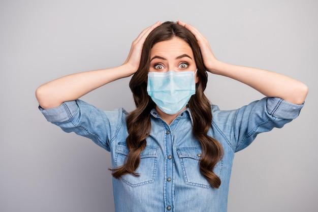 Portrait en gros plan d'elle, elle est gentille, inquiète, malade, malade, fille aux cheveux ondulés, portant un masque de sécurité en gaze, risque biologique, maladie contagieuse, syndrome de grippe, concept, pandémie, fond de couleur gris isolé