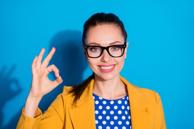 Portrait en gros plan d'elle, elle, jolie, charmante, charmante, joyeuse, joyeuse, gestionnaire des ressources humaines, montrant un poste vacant de carrière ok-signe, une annonce d'embauche isolée, brillante, éclatante, fond de couleur bleu vif