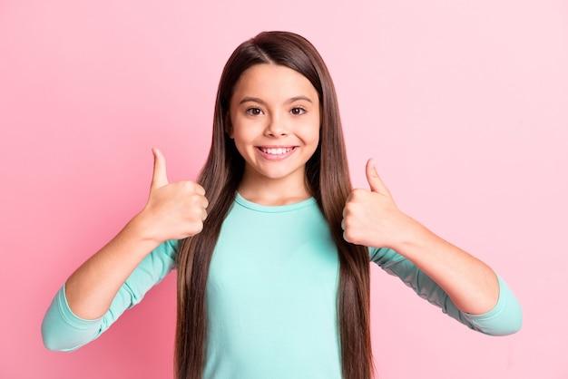 Portrait en gros plan d'elle, elle, jolie, jolie, confiante, joyeuse, joyeuse, aux cheveux longs, montrant deux doubles pouces annonce une solution parfaite isolée sur fond de couleur pastel rose