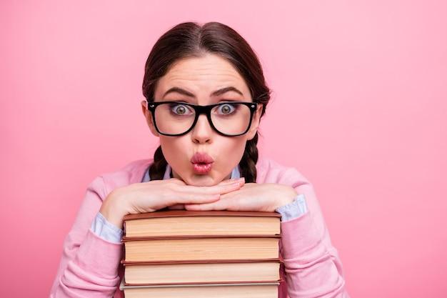 Portrait en gros plan d'elle, elle, jolie, jolie, étonnée, génie intelligent, adolescente aux cheveux bruns, tenant la main, s'appuyant sur les lèvres de la moue scientifique du livre de piles isolées sur fond de couleur pastel rose