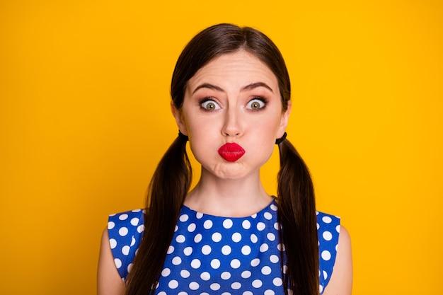 Portrait en gros plan d'elle elle jolie jolie jolie fille glamour funky humoristique gaie grimaçante tenant de l'air dans les joues isolées sur fond de couleur jaune vif brillant éclatant