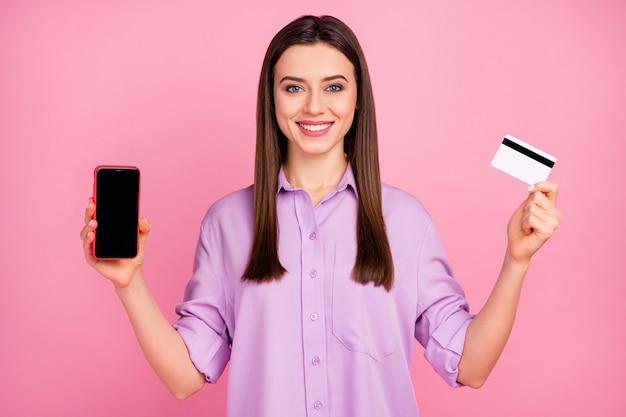 Portrait en gros plan d'elle elle jolie jolie jolie jolie jolie jolie jolie fille aux cheveux longs joyeuse joyeuse et joyeuse démontrant à l'aide d'une carte bancaire cellulaire achetant en ligne isolée sur fond de couleur pastel rose