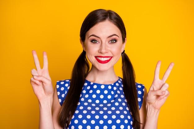 Portrait en gros plan d'elle, elle, jolie, jolie, optimiste, joyeuse, joyeuse, montrant une partie de symbole à double signe v isolée sur un fond de couleur jaune vif et brillant