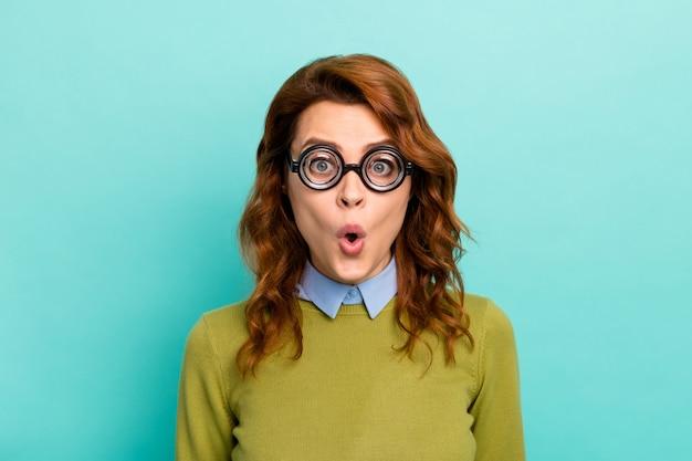 Portrait en gros plan d'elle, elle séduisante et étonnée d'une drôle de fille aux cheveux ondulés portant des lunettes épaisses, une expression de stupeur décontractée, isolée sur un fond de couleur turquoise sarcelle éclatant et brillant