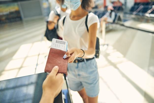 Portrait en gros plan d'un employé de l'aéroport donnant un passeport et un billet d'avion au touriste avec sac à dos
